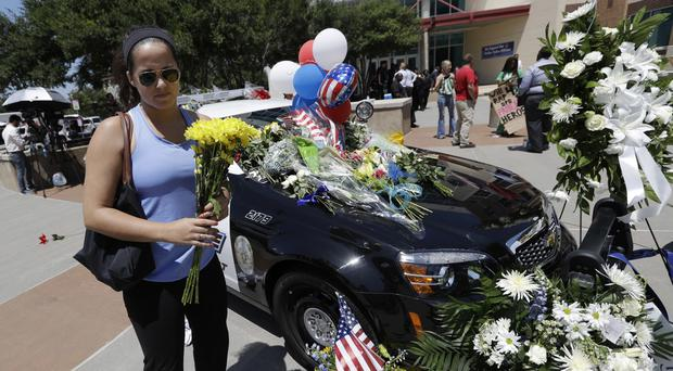 A woman places flowers at the Dallas police headquarters, following the killing of five officers (AP)