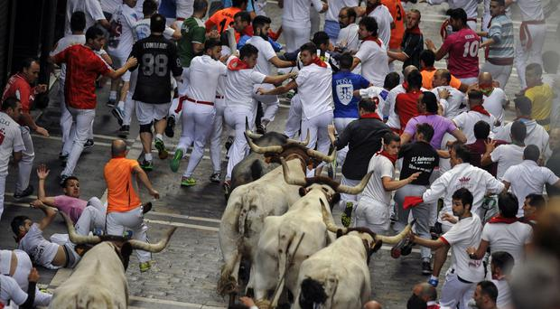 Revellers run during the third running of the bulls at the San Fermin festival in Pamplona, northern Spain (AP)