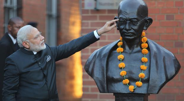 Indian prime minister Narendra Modi points at a bust of Mahatma Gandhi on a visit to Constitutional Hill in Johannesburg (AP)