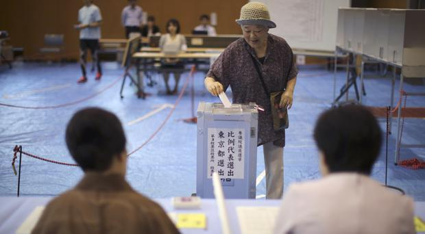 A voter casts her ballot in Japan's upper house parliamentary election at a polling station in Tokyo (AP)