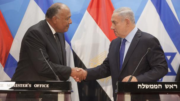Israeli Prime Minister Benjamin Netanyahu shakes hands with Egyptian foreign minister Sameh Shoukry, left, in Jerusalem (AP)