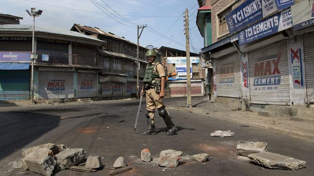 An Indian soldier stands guard near a roadblock set up by Kashmiri protesters, during a curfew in Srinagar (AP)