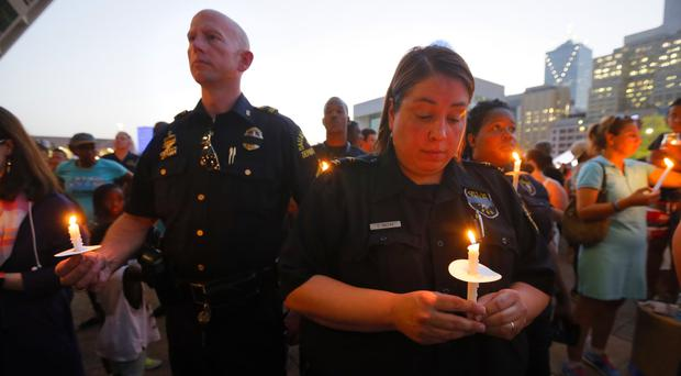 Police officers take part in a candlelight vigil at City Hall in Dallas (AP)