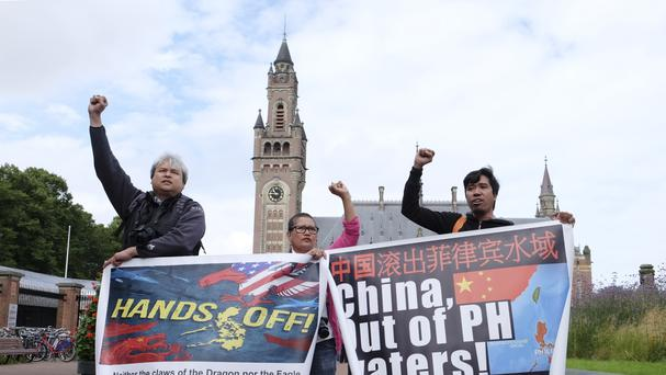 Protesters stand outside the Peace Palace in The Hague ahead of a ruling by the Permanent Court of Arbitration on the dispute between China and the Philippines over the South China Sea (AP)