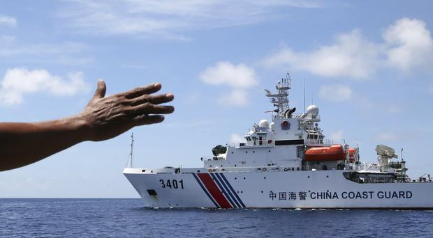 A member of the Philippines navy signals towards a Chinese coastguard vessel blocking them from entering Second Thomas Shoal in the South China Sea (AP)