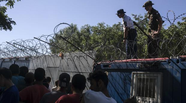 Hungarian police and army officers oversee the distribution of food as people queue inside a migrant camp at Serbia's border with Hungary, in Horgos, Serbia (AP)