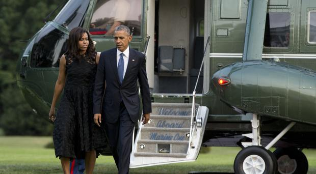 US President Barack Obama and wife Michelle arrive back at the White House after attending a memorial service for five police officers shot dead in Dallas (AP)