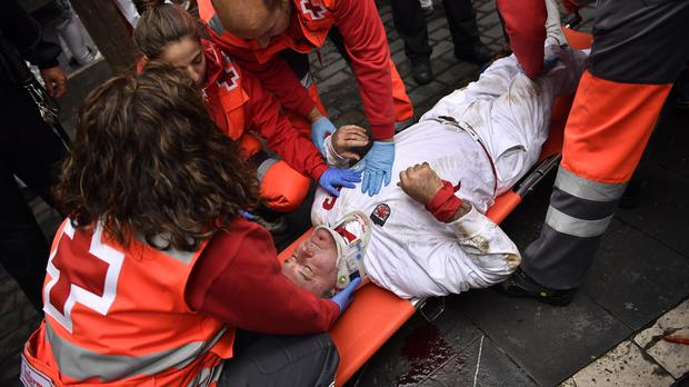 An injured reveller is tended to by medics during the seventh running of the bulls at the San Fermin festival in Pamplona, Spain (AP)