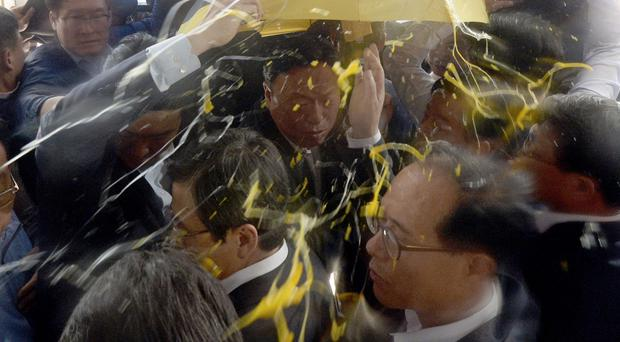 South Korean PM Hwang Kyo-ahn, bottom centre, is shielded by his bodyguards from eggs thrown by residents at Seongju County Office (Kang Jong-min/Newsis via AP)