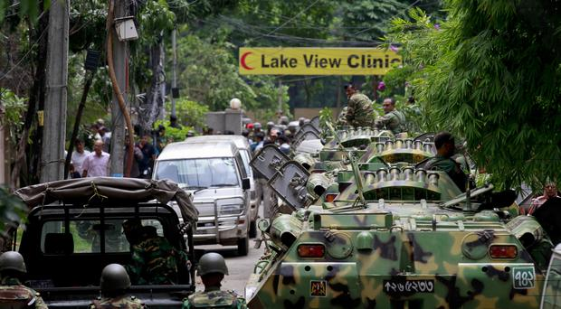 Bangladeshi soldiers ride armoured vehicles as they prepared to raid a restaurant where armed gunmen took hostages in Dhaka (AP)