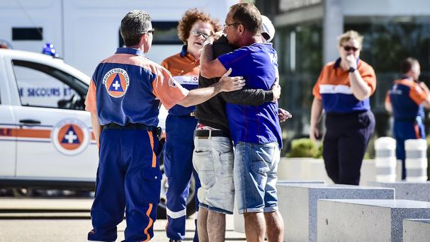 Relatives are comforted by medical staff outside the Pasteur hospital in Nice, where 18 people remain in a life-threatening condition