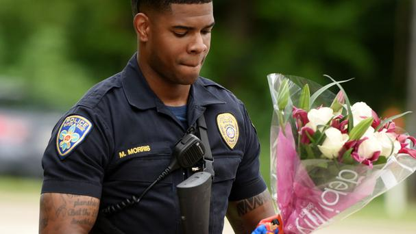 Baton Rouge officer Markell Morris holds a bouquet of flowers and a Superman action figure left at the Our Lady of the Lake Hospital where the police casualties were brought (The Times/AP)