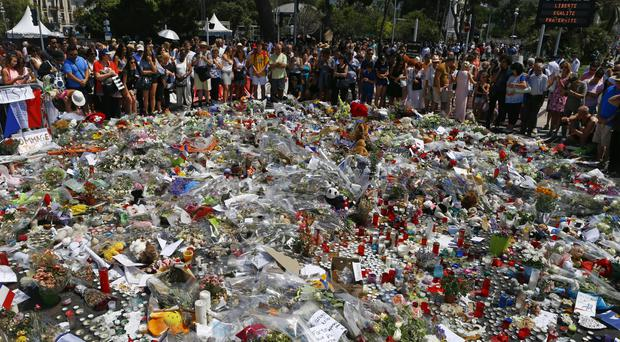 People gather at the makeshift memorial to victims of the Nice truck attack (AP)