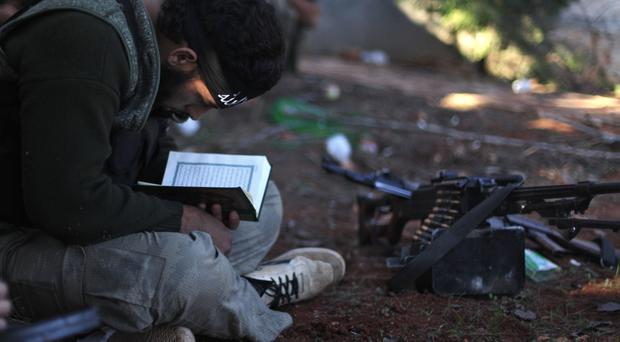 A Syrian rebel reads the Koran during clashes with government forces in Aleppo (AP)