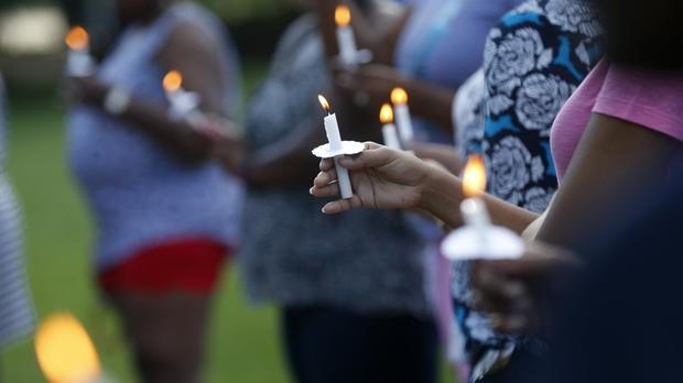 People attend a candlelight vigil for Baton Rouge police officer Montrell Jackson outside the school he attended (AP)