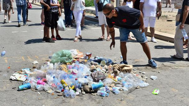 A man spits on a pile of rubbish left to signify the spot where the truck driver was killed (AP)