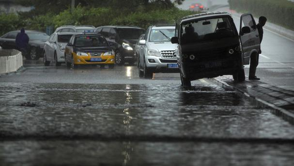 Cars at a flooded underpass during a rainstorm in Beijing, as China suffered serious flooding (AP)