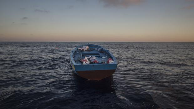 A wooden boat used by refugees to leave Libya drifts abandoned after a rescue operation to save migrants on the Mediterranean Sea (AP)