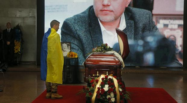 A man draped in a Ukrainian national flag stands at the coffin of Pavel Sheremet in Kiev (AP)