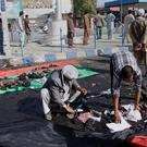 Afghans gather property left behind by victims of an explosion that struck a protest march
