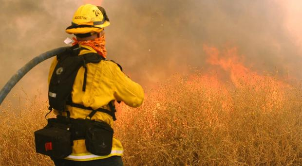 A Los Angeles County firefighter tackles a blaze in Santa Clarita (AP)