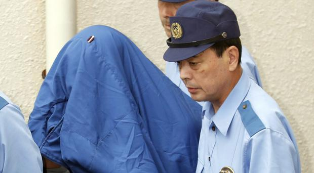 Police cover massacre suspect Satoshi Uematsu's head with a jacket as he is moved to face prosecutors (Kyodo News/AP)