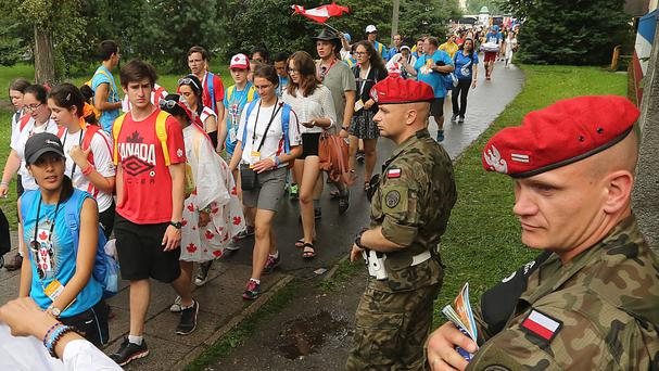 Soldiers watch pilgrims heading to the opening Mass for the World Youth Day in Krakow (AP Photo/Czarek Sokolowski)