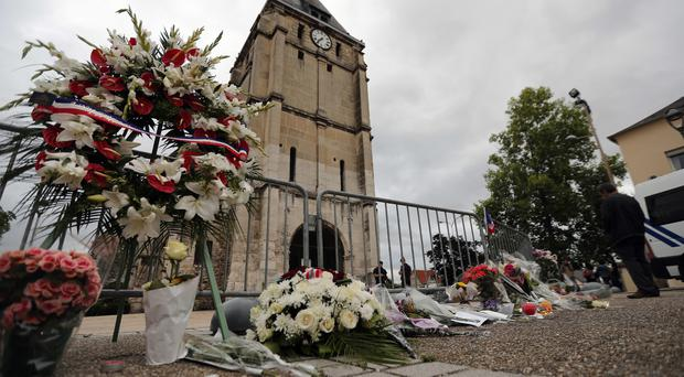 Flowers next to the church where a hostage-taking left a priest dead in Saint-Etienne-du-Rouvray, Normandy, France (AP)