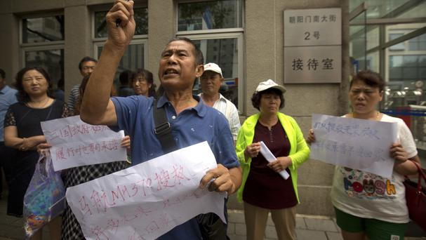 People hold signs protesting over the handling of the search for Malaysia Airlines Flight 370 outside China's Ministry of Foreign Affairs in Beijing (AP)