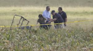The partial frame of the hot air balloon is visible above crops as investigators comb the wreckage (Austin American-Statesman/AP)