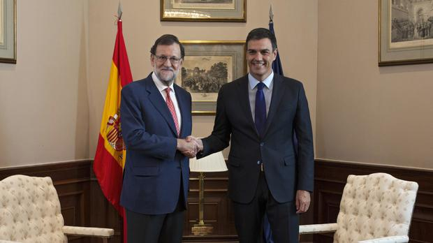 Spain's acting PM Mariano Rajoy, left, shakes hands with Socialist Party leader Pedro Sanchez before their meeting in Madrid (AP)