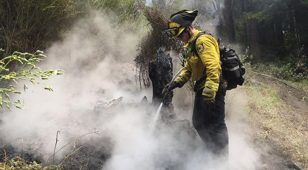 Novato Fire District firefighter Kyle Marshall tackling a blaze in Big Sur (AP)