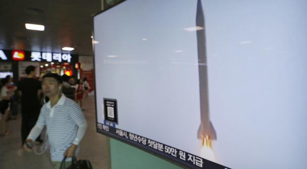 A man walks by a TV news programme with footage of a North Korean rocket launch at the Seoul railway station (AP)