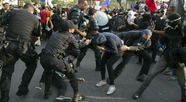 Demonstrators scuffle with riot police during a protest against the money spent on the Rio Olympics (AP)