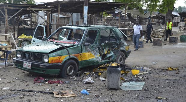 People walk past a damaged car at the site of a bomb explosion in Maiduguri, Nigeria (AP)