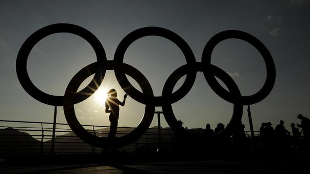 A woman is silhouetted by the setting sun in the Olympic Park in Rio (AP)