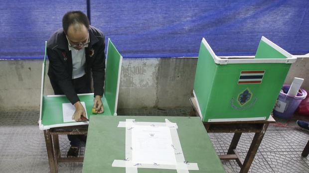 A Thai official prepares a booth for voting in a referendum on a new constitution, at a polling station in Bangkok (AP)