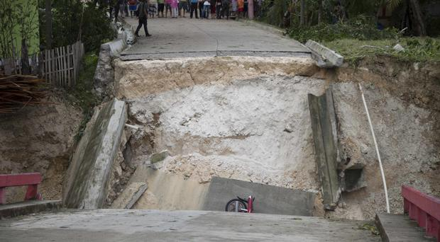 A motorcycle lies in the debris of a collapsed bridge brought down by Hurricane Earl in Guatemala, before it moved on to Mexico (AP)