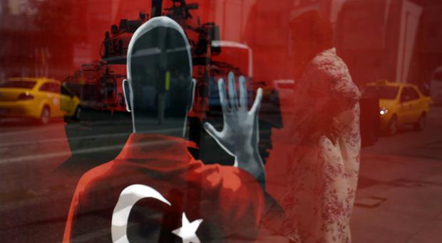 A woman is reflected in a poster made for an anti-coup rally, at Taksim Square in Istanbul (AP)