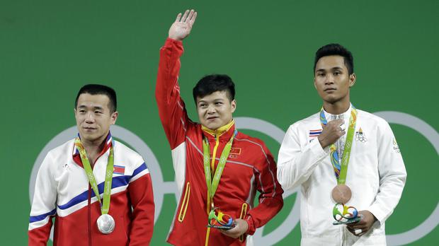Men's 56kg weightlifting gold medallist Long Qingquan, of China, centre, with silver medallist Om Yun Chol, of North Korea, left, and bronze medallist Sinphet Kruaithong, of Thailand, right (AP)