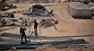 Palestinian workers rebuild a house which was destroyed during fighting between Israel and Hamas, in Gaza City (AP)