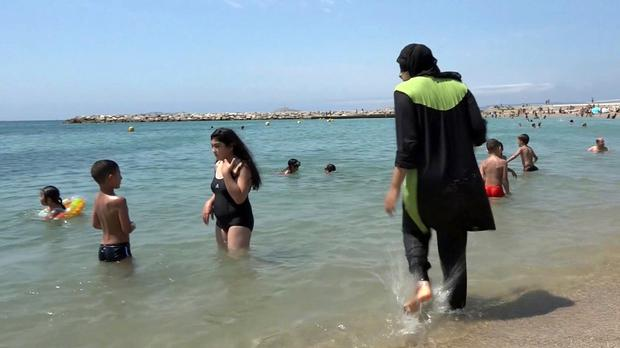 A young Muslim bather gets into the sea wearing a full-body swimsuit in Marseille (AP)