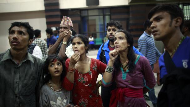 Family members of passengers on a bus that crashed on a mountain road look at a list of survivors airlifted for treatment at a hospital in Kathmandu, Nepal (AP)