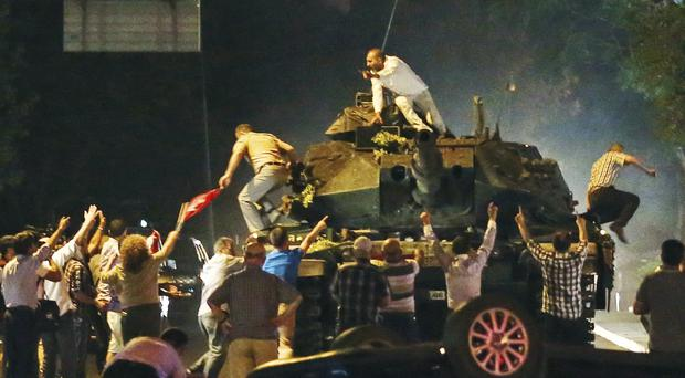 A tank moves into position as Turkish people climb onto it, attempting to stop the military coup in July (AP)