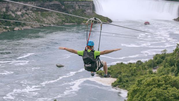 A tourist suspended above the water from zip lines makes his way towards the Horseshoe Falls on the Ontario side of Niagara Falls (Kien Tran/WildPlay Ltd via AP)