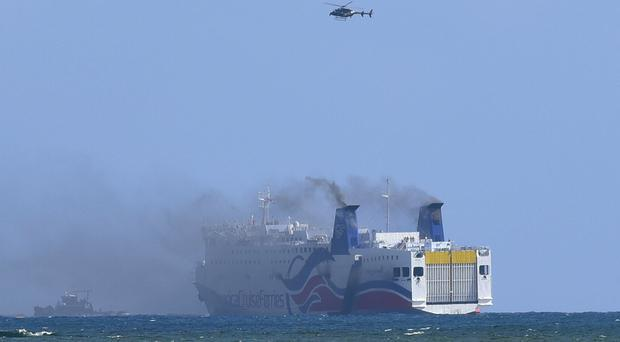 Smoke spills from the cruise ship Caribbean Fantasy off the coast of San Juan, Puerto Rico (AP)