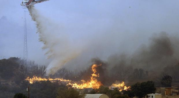A helicopter drops retardant and water over flames in West Cajon Valley, California (AP)