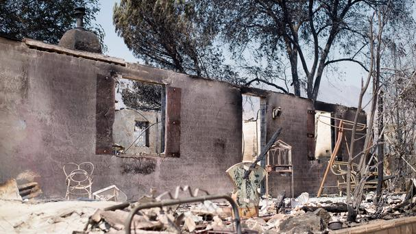 A burned-out residence stands amid rubble on Highway 138 after the Blue Cut Fire burned through Phelan, California (AP)