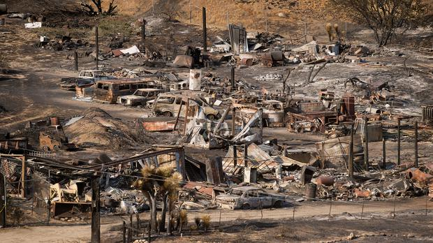 Scorched cars and trailers line a residential street in Phelan, California (AP)