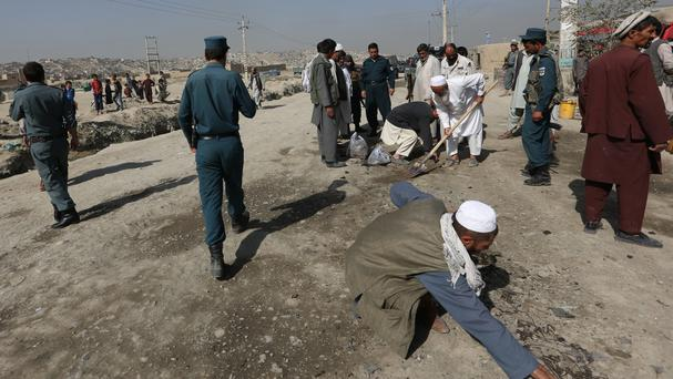 Afghan security police inspect the site of bomb blast on the outskirts of Kabul (AP)